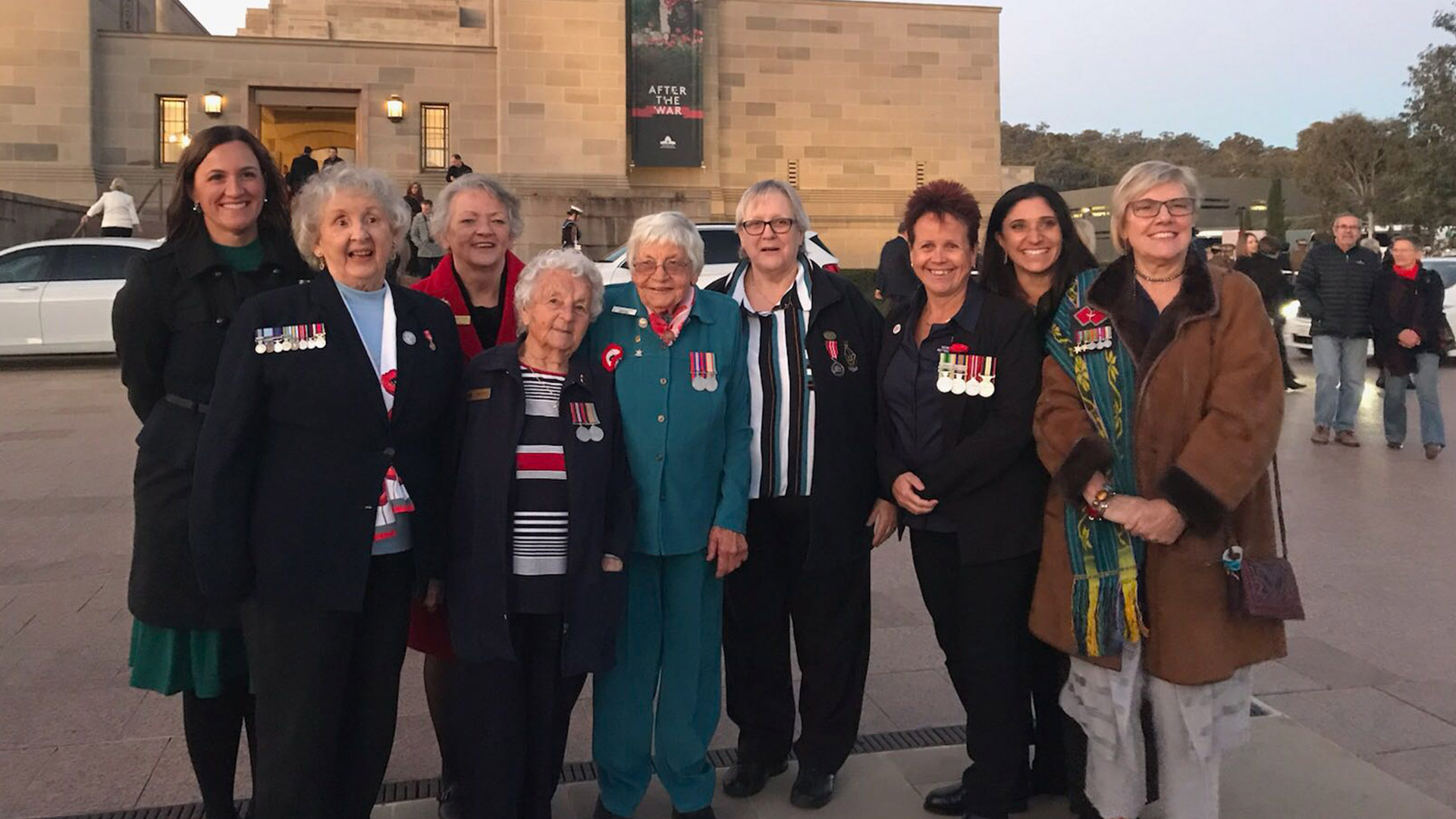 9 women wearing military medals stand together proudly looking into the camera in front of the Australian war memorial.