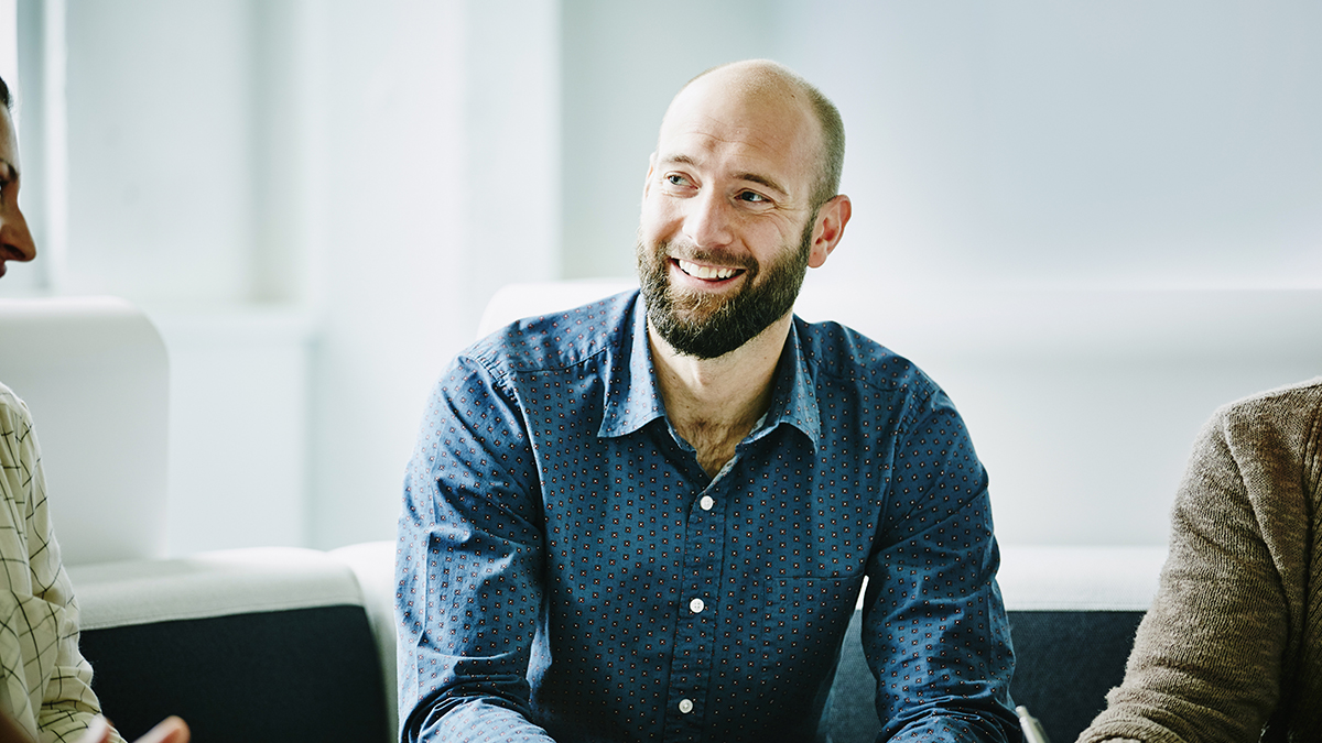 Man in his 30s smiling at work, sitting at desk