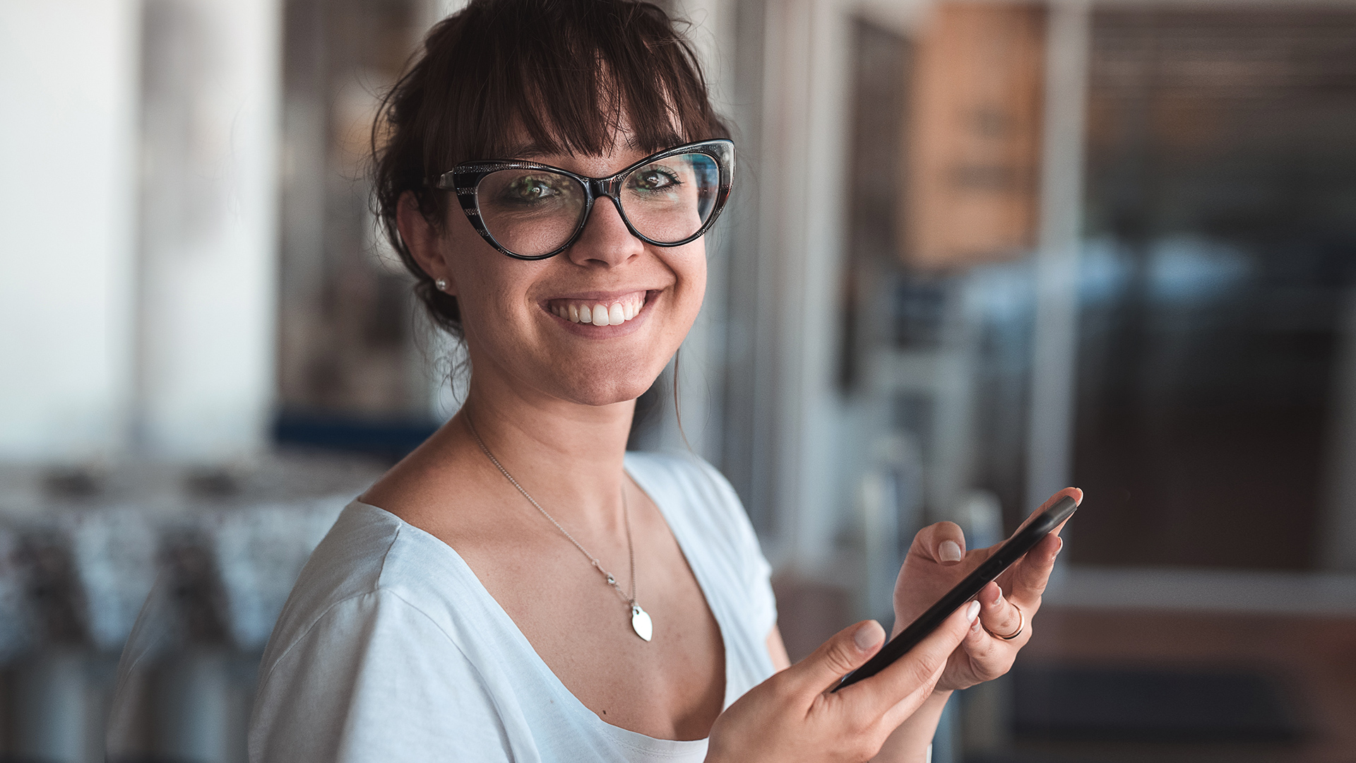 Woman with glasses smiling after using super calculator