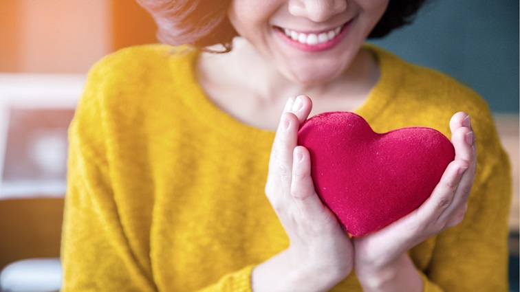 A woman wearing a yellow jumper is holding a plush red heart and smiling