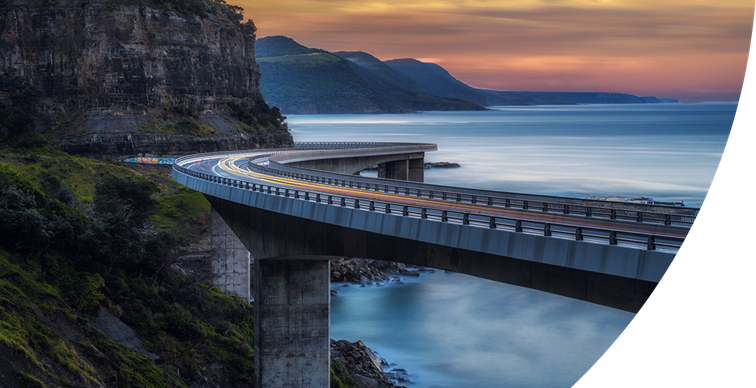 Sunset over the sea cliff bridge along the Australian Pacific Ocean coast with lights trails from cars