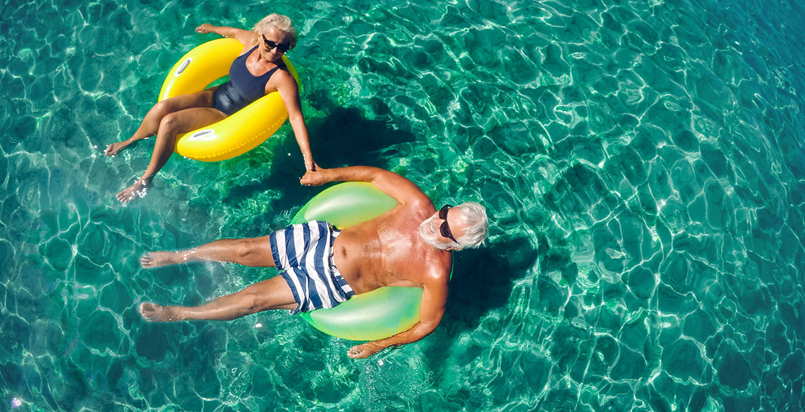 two older people floating in floating rings on a wide green ocean